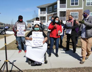 Manisha Divecha, 33, is joined by supporters outside her apartment complex in Malvern
