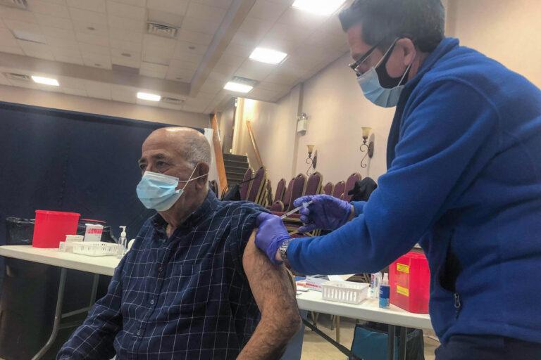 Joseph Dymowski, co-owner of Centennial Pharmacy, vaccinates Costa Monsour, a parishioner at St. Maron Maronite Catholic Church. (Nina Feldman / WHYY)