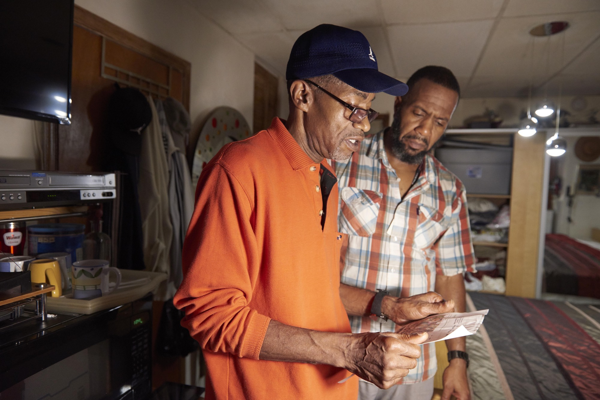 Walter Briggs (right) shows community health worker Orson Brown (left) a high utility bill during a home visit