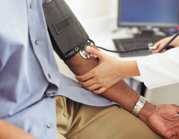 A white health care worker takes the blood pressure of a Black patient