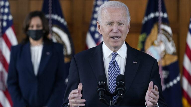 President Biden speaks while Vice President Harris is seen in the background.