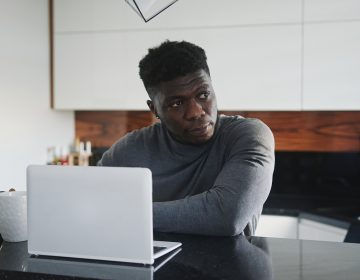 A young Black man working on laptop in his apartment