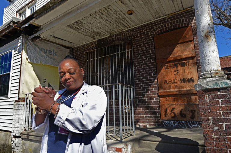 Carlita Smith holds her hands together in prayer in front of a Camden home