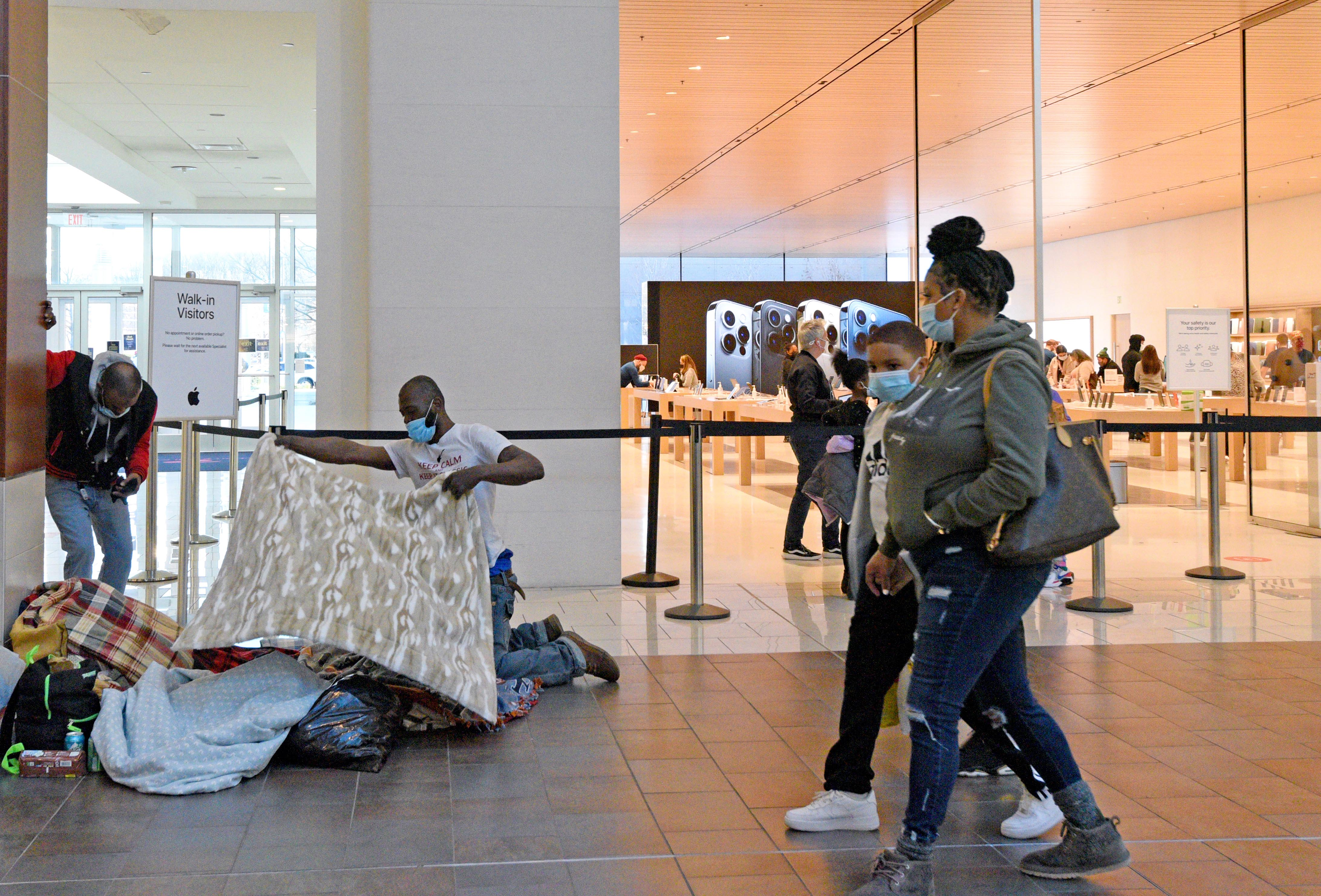 Unhoused individuals spread blankets on the floor of the Cherry Hill Mall