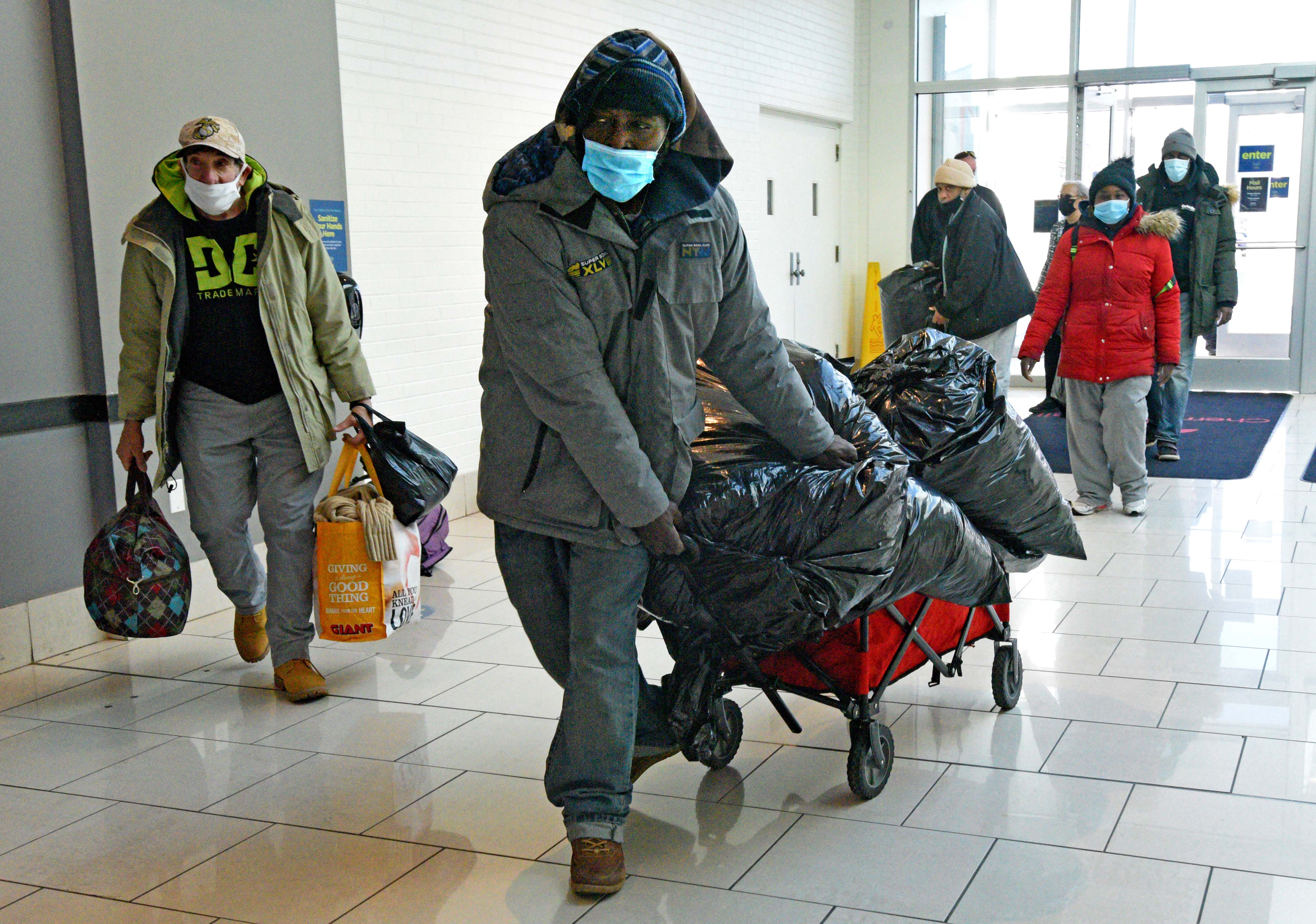 Unhoused individuals, led by Tawanda Jones, bring blankets and their belongings into the Cherry Hill Mall