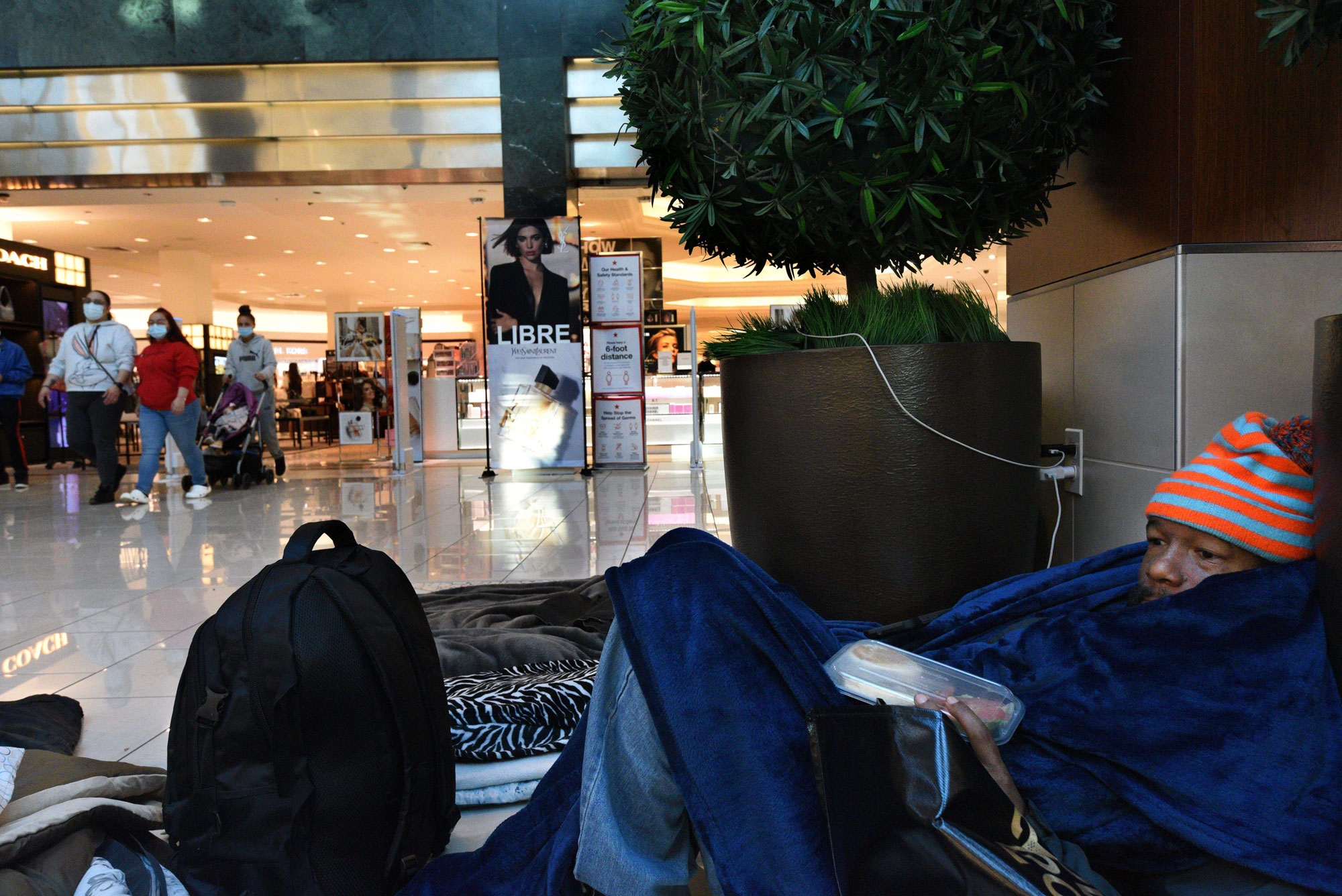 An unhoused individual reclines on the floor of the Cherry Hill Mall
