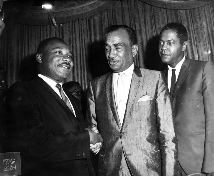 Dr. Martin Luther King Jr. and Cecil B. Moore shake hands as Georgie Woods watches in 1965 at the Bellevue-Stratford Hotel in Philadelphia. (Courtesy of Temple University Libraries, Charles L. Blockson Afro-American Collection)