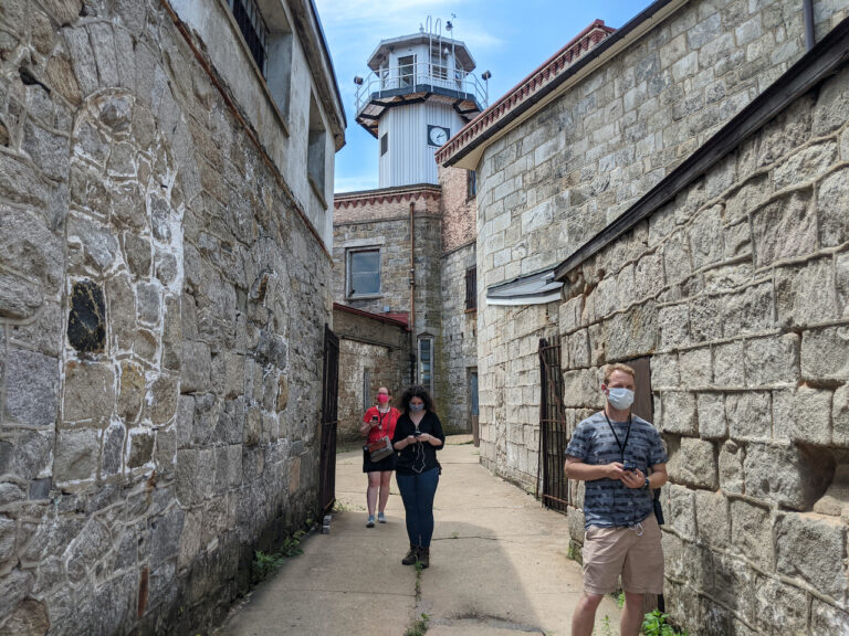 Visitors in the Eastern State Penitentiary courtyard wearing face masks.