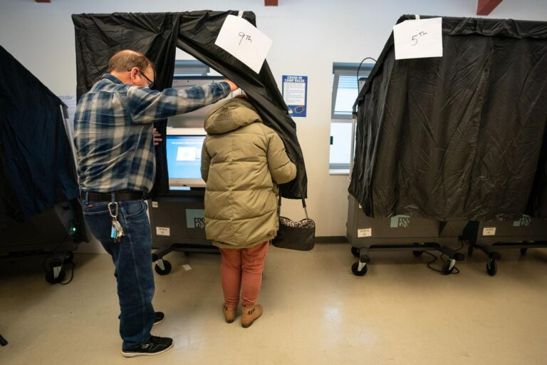 A person enters the voting booth to cast their ballot