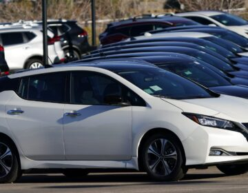 A line of Leaf electric vehicles sits at a Nissan dealership