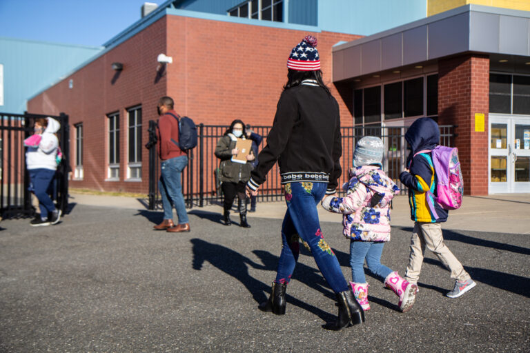 A parent holds their child's hand as they walk to school