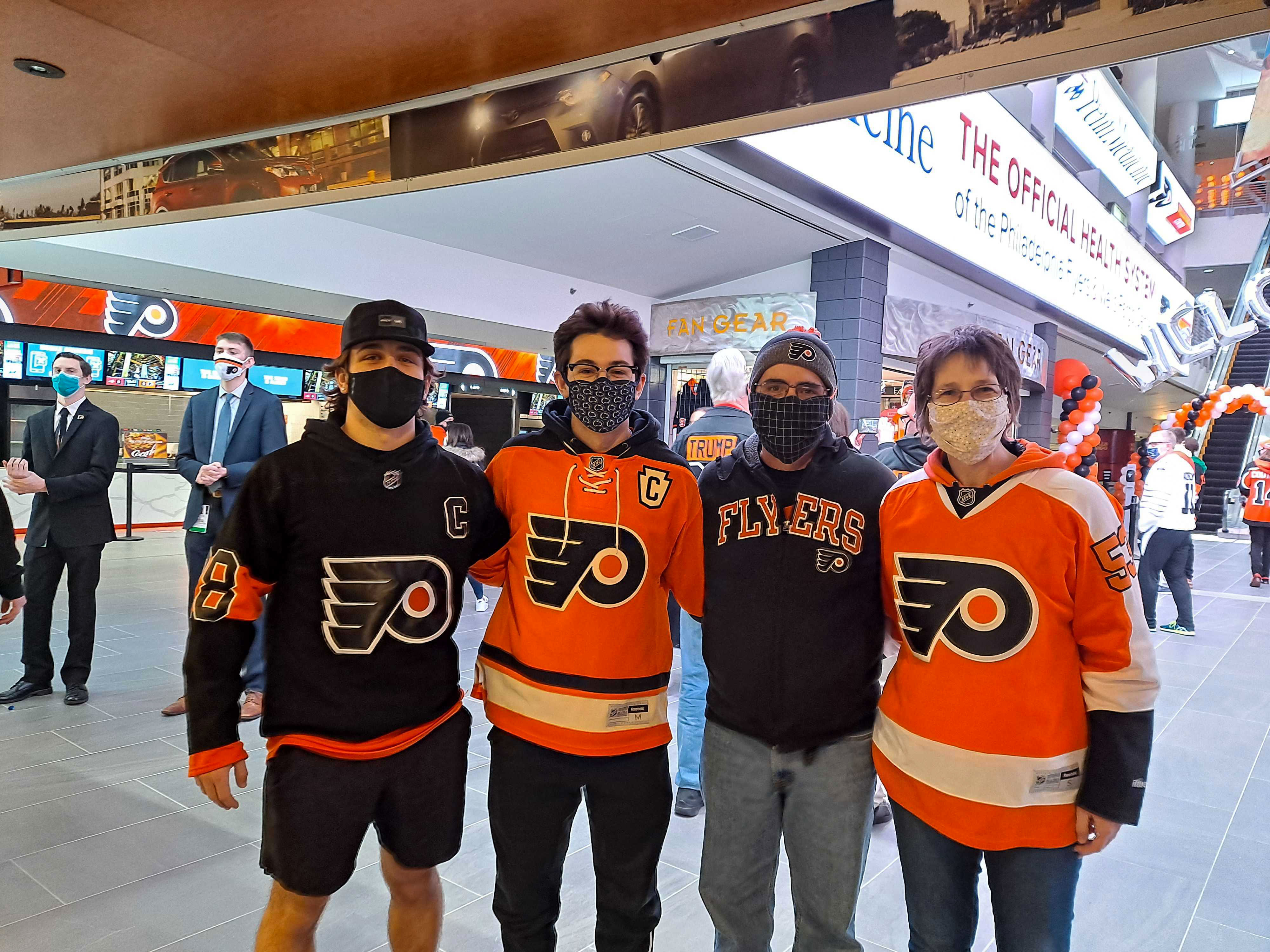 A group of Flyers fans stand side-by-side inside Wells Fargo Center