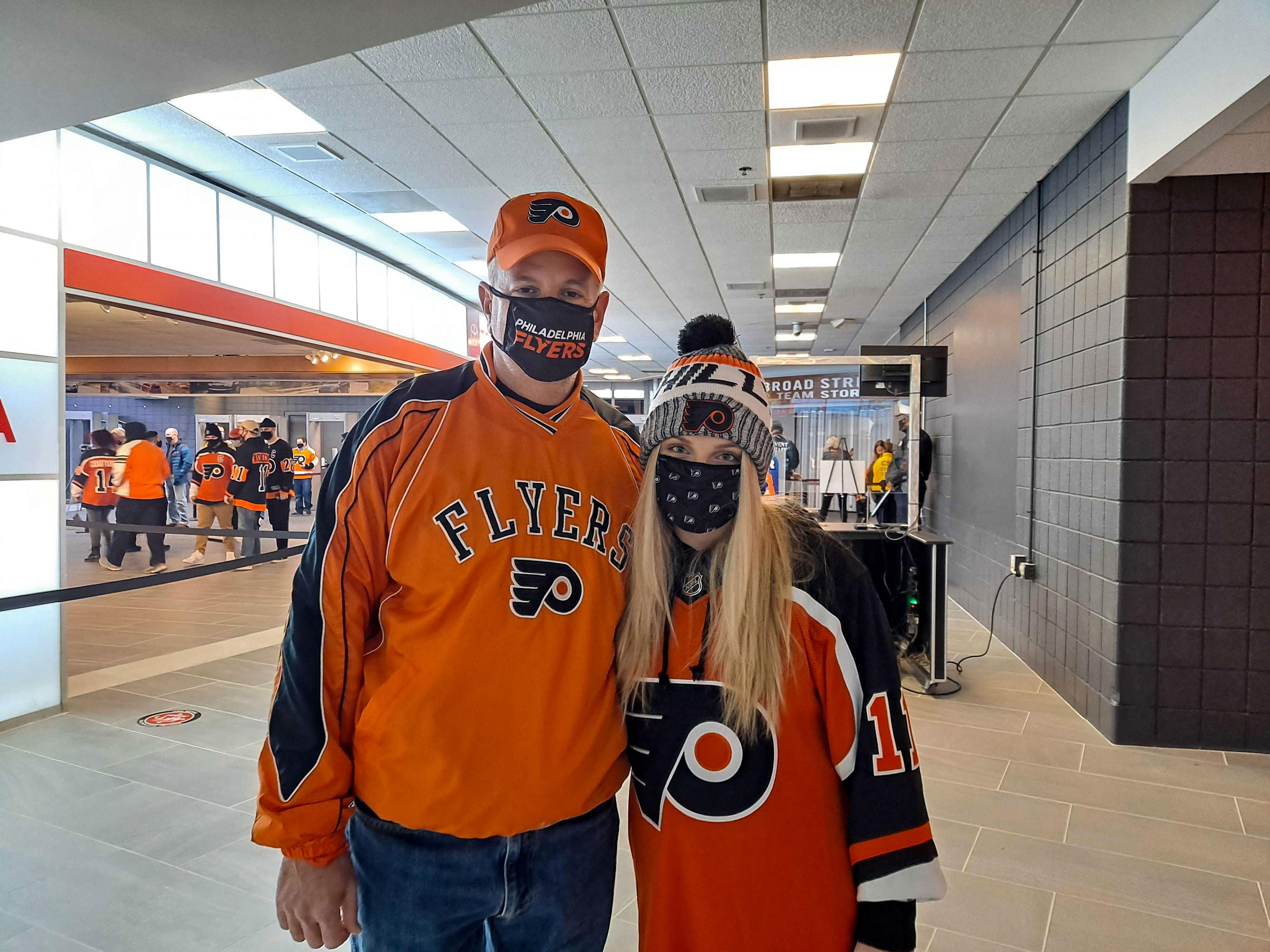 Joe Arnone and his daughter, wearing Flyers gear inside Wells Fargo Center