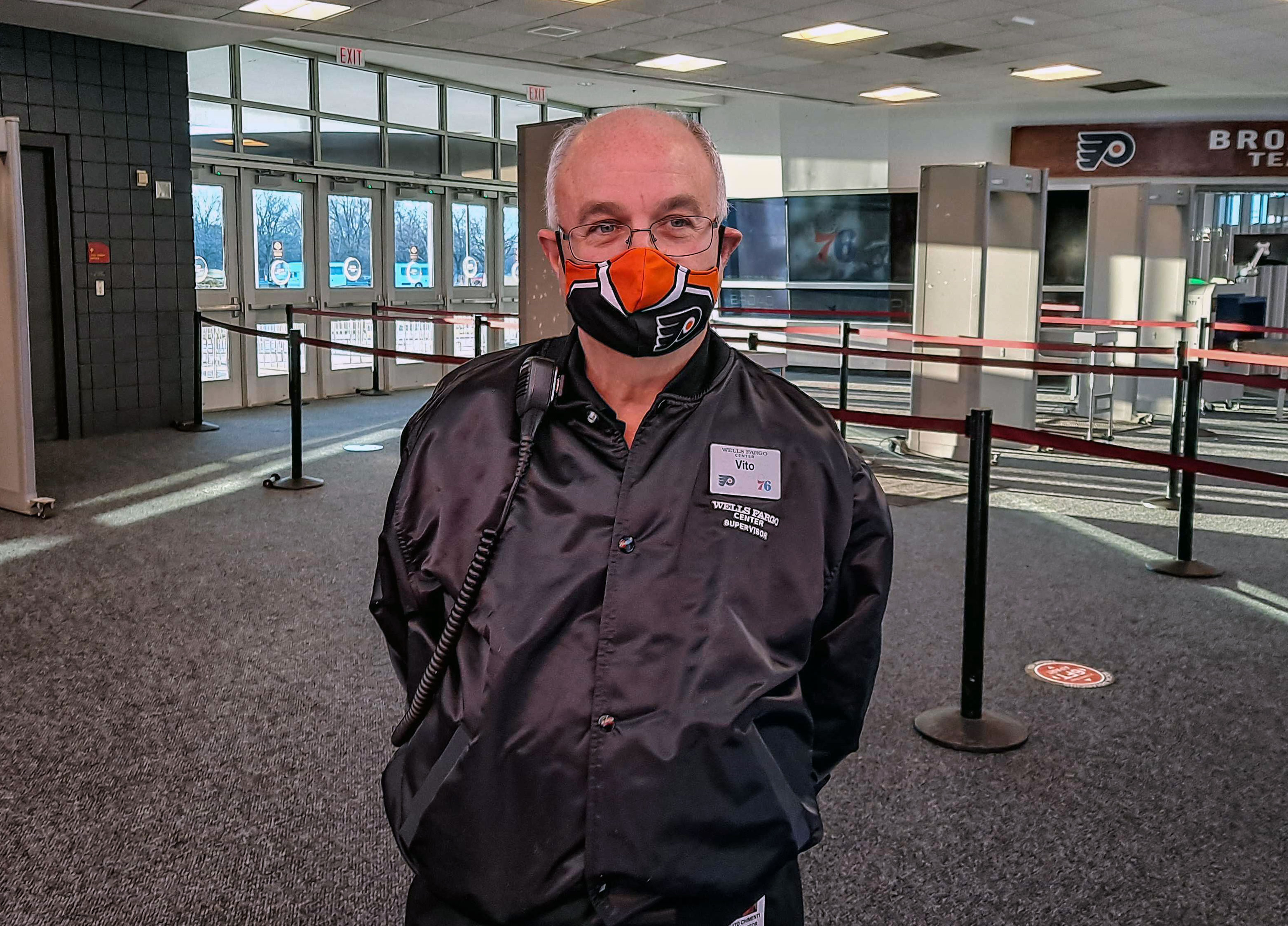 Vito Chimenti, wearing a face mask, stands inside Wells Fargo Center