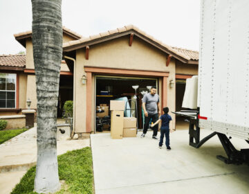 Young son helping father move items from moving truck into new house