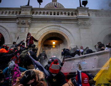 Pro-Trump rioters clash with police and security forces as people storm the U.S. Capitol on Jan. 6. Federal investigators say they expect even more people will be charged in connection with the insurrection. (Brent Stirton/Getty Images)