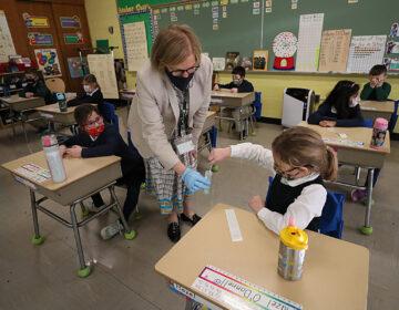 A student gives her coronavirus swab to Helenann Civian