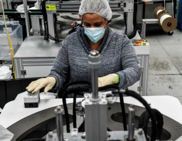 An employee makes respiratory masks in a family-owned medical equipment factory