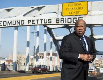 John Lewis stands on the Edmund Pettus Bridge