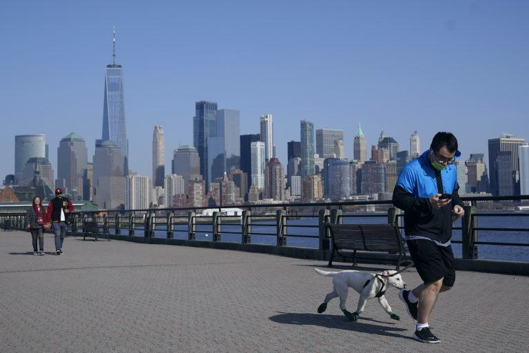 A man jogs with his dog at Liberty State Park in Jersey City