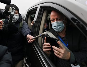 Peter Daszak holds up a phone from the passenger seat of a car while wearing a mask