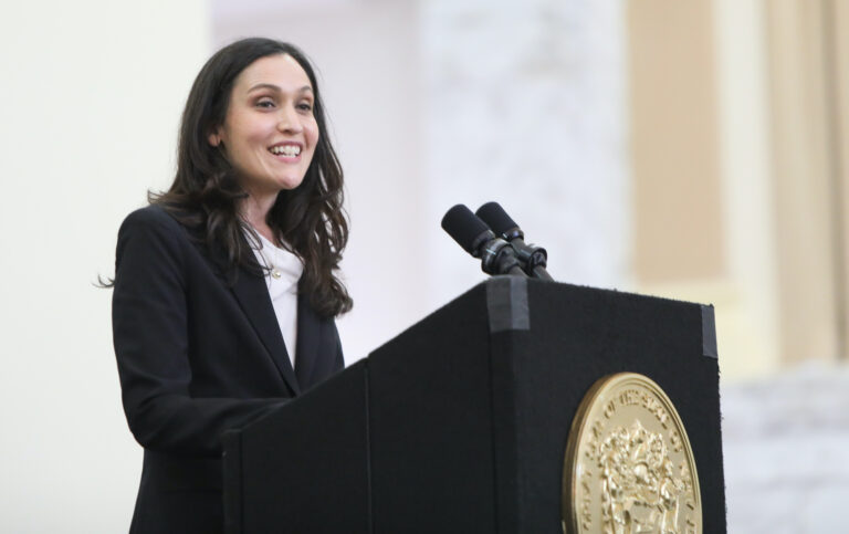 Rachel Wainer Apter speaks from a podium at Ruth Bader Ginsburg Hall