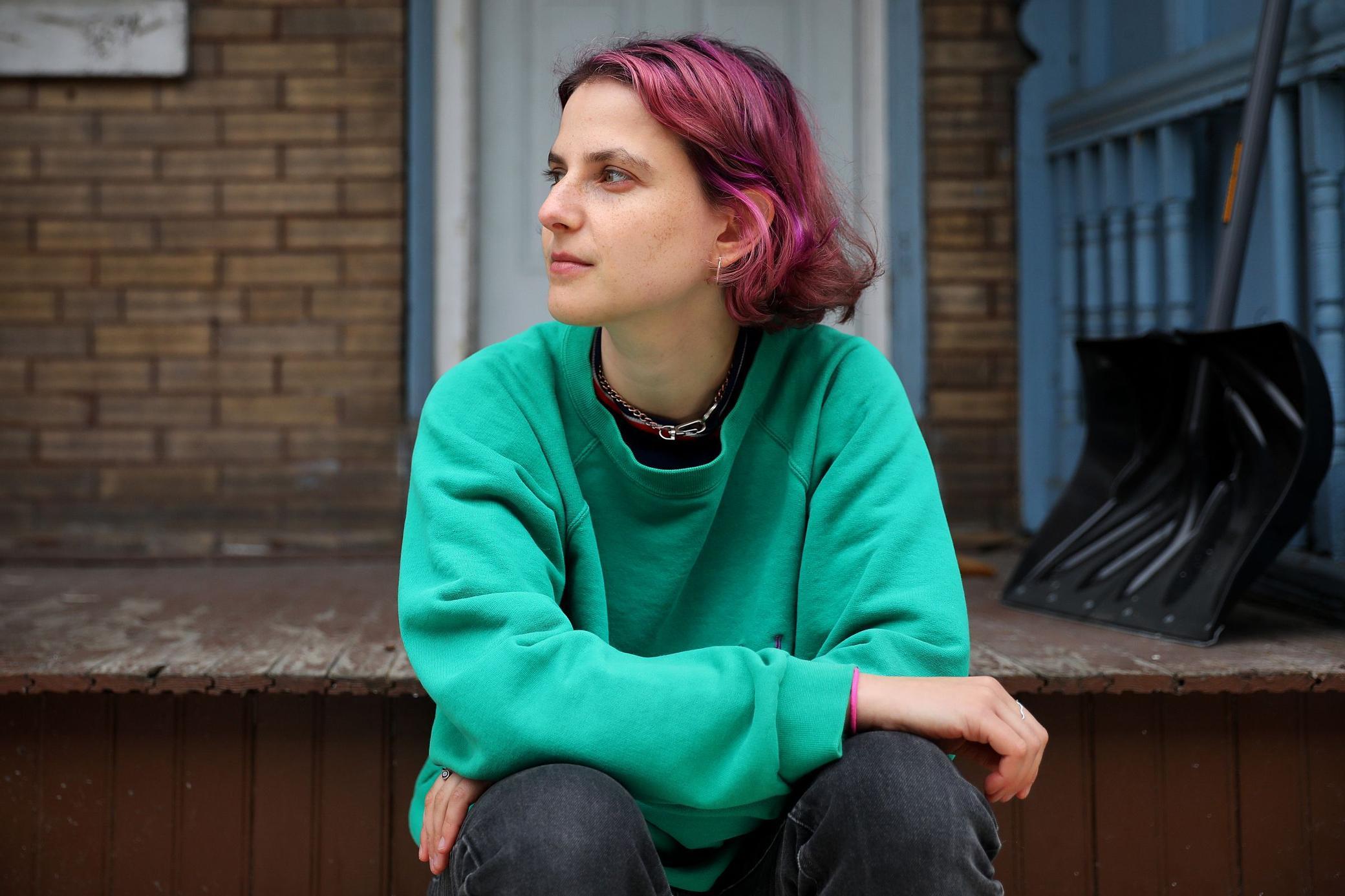 Rachel Weisberg sits on a stoop