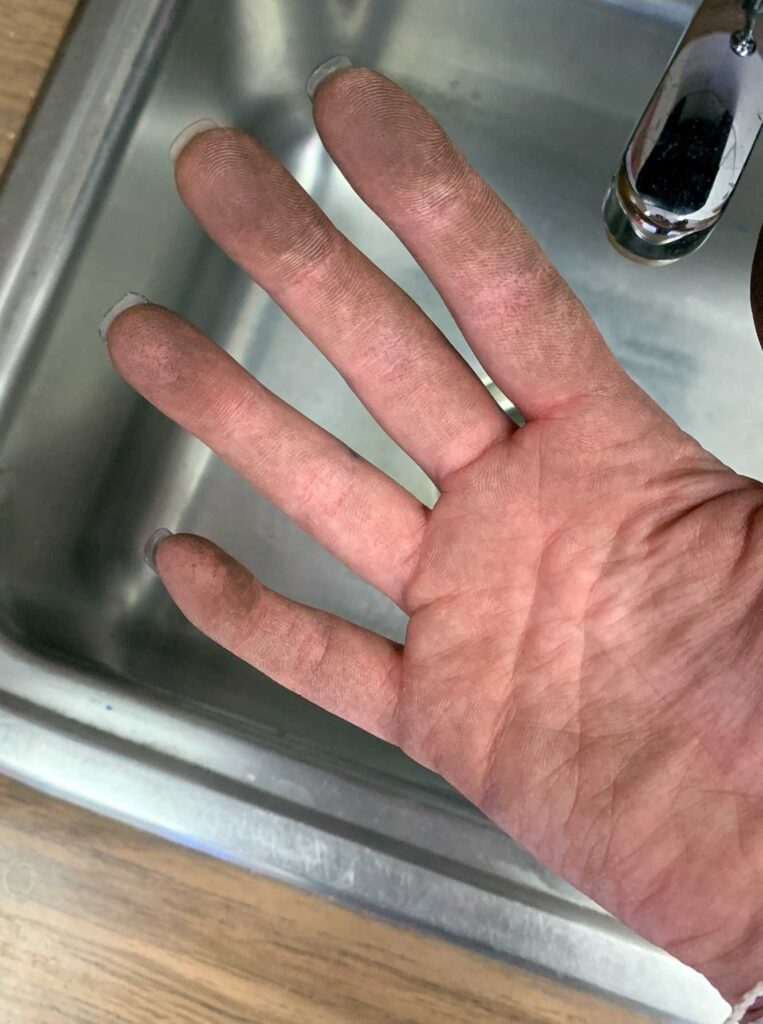 Rutherford's hands covered in dust after cleaning her classroom