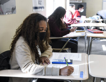 Giani Clarke, 18, a senior at Wilson High School in West Lawn, Pa., takes a test in her AP statistics class earlier this month. The desks are doubled as a way to provide more social distancing. (MediaNews Group/Reading Eagle vi/MediaNews Group via Getty Images)