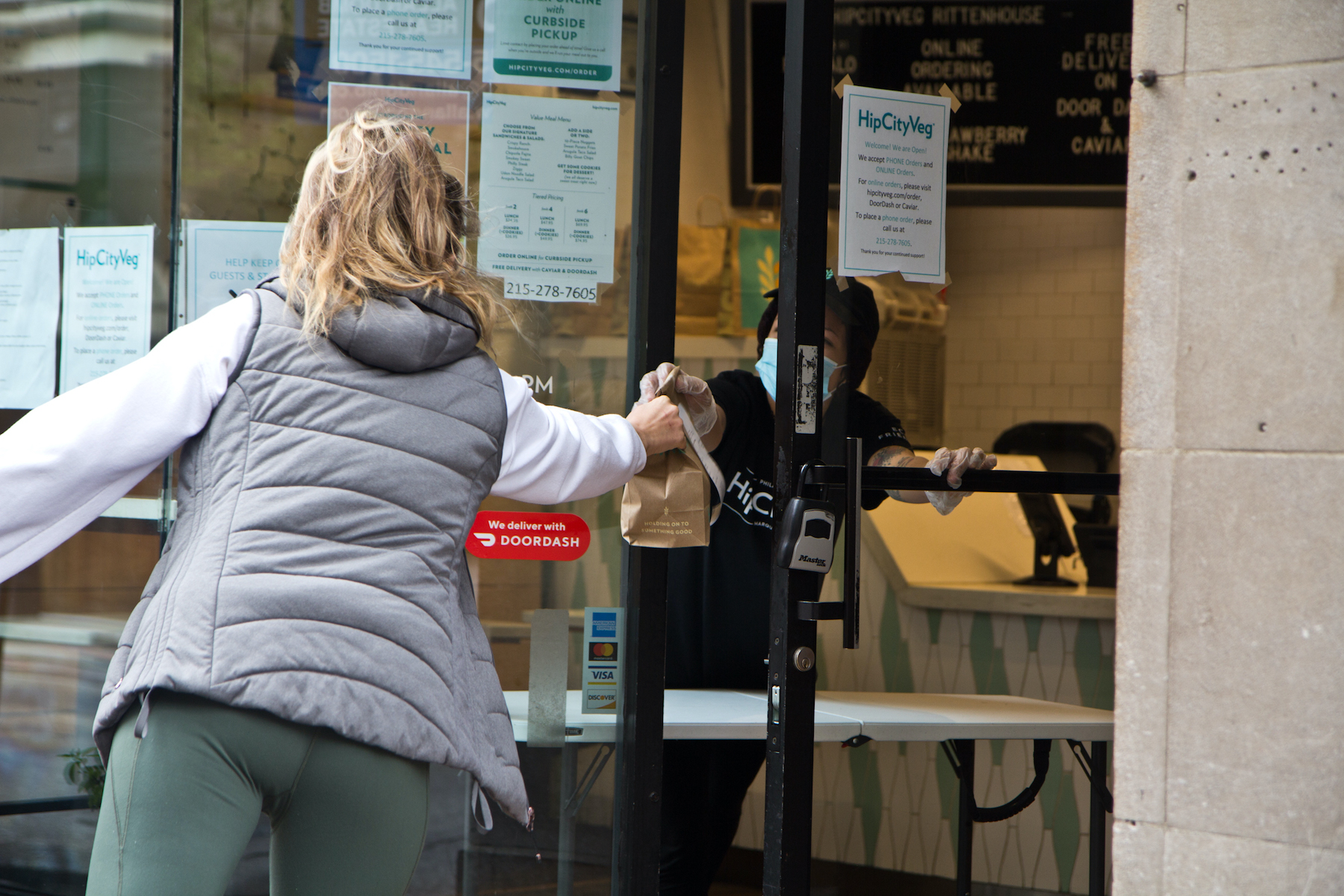 An employee hands off a to-go order through the door of HipCityVeg