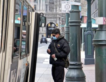 A passenger boards a SEPTA bus on Market Street near City Hall. (Emma Lee/WHYY)