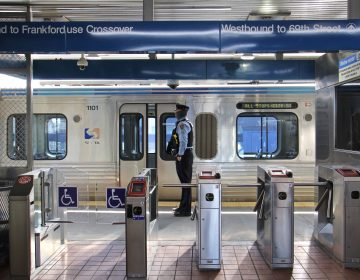 A SEPTA police officer stands on the platform of the Somerset stop on the Market-Frankford line. (Emma Lee/WHYY)
