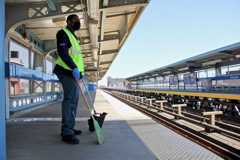 A SEPTA employee stands by with broom and basket at the spruced-up Somerset Station on the Market-Frankford line. (Emma Lee/WHYY)