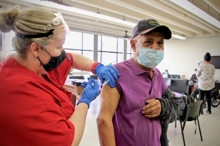 Eduardo Delgado gets his COVID-19 vaccination from Gail Bagnato