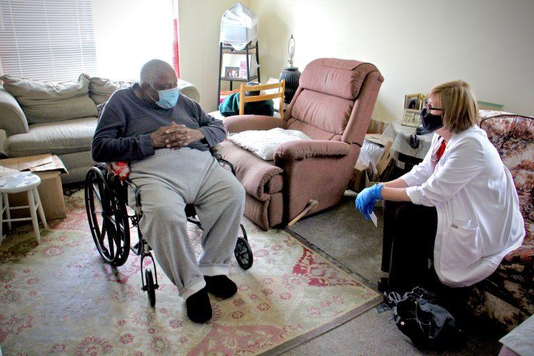 Rebecca Bryan of Rutgers School of Nursing sits with 86-year-old Turner Pittman