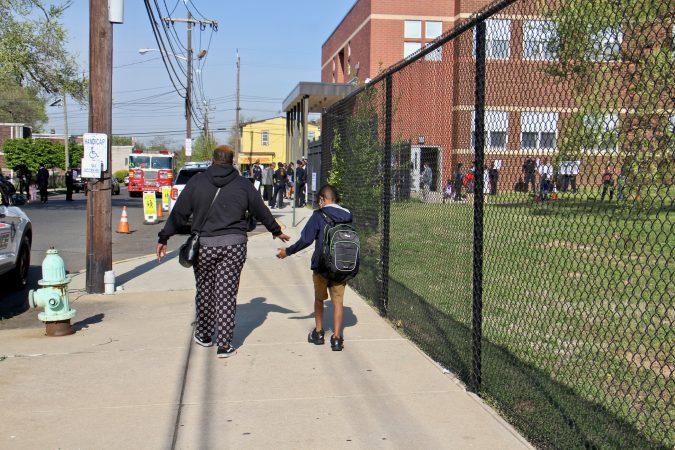 Ni G Kinard escorts her son, Keith Kinard III, 8, to opening day
