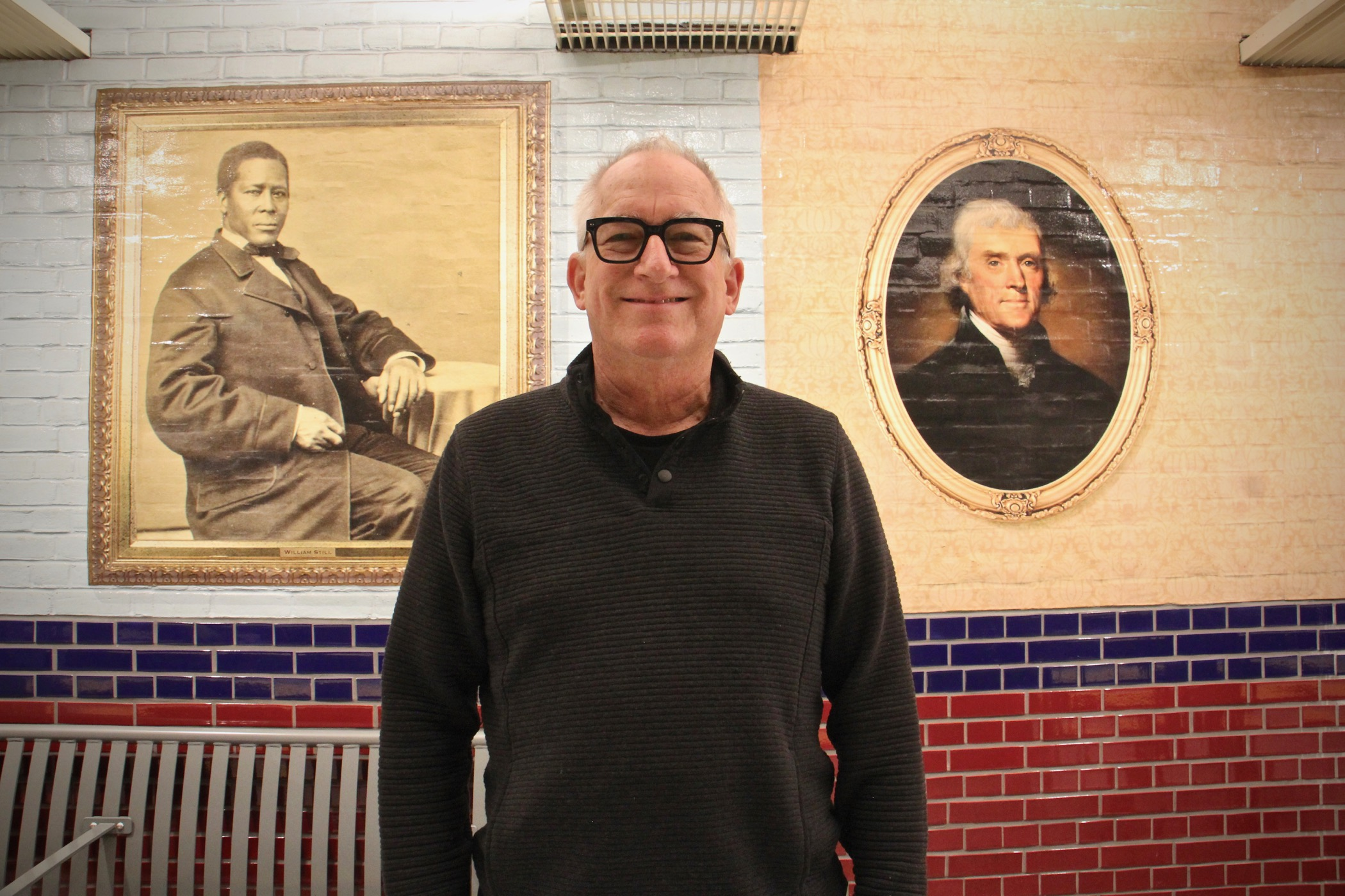 Artist Tom Judd created the murals for the Independence Hall SEPTA Station. He stands between portraits of abolitionist William Still and founding father Thomas Jefferson. (Emma Lee/WHYY)
