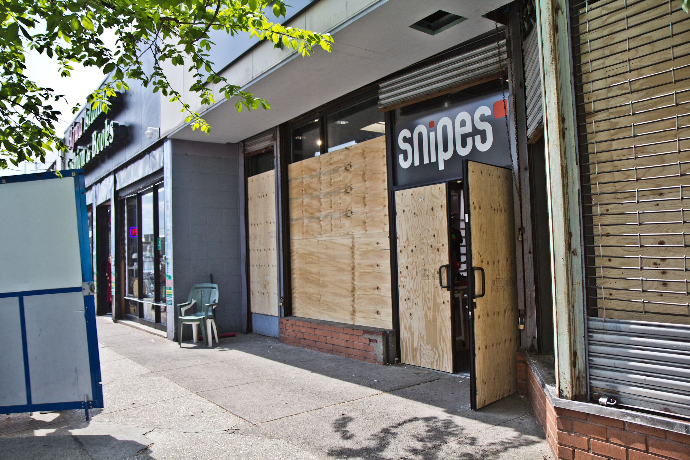 Snipes, Foot Locker and the Puma store on 52nd Street in West Philadelphia remained boarded up the day after the verdict was delivered in the trial of Derek Chauvin on April 21, 2021. (Kimberly Paynter/WHYY)
