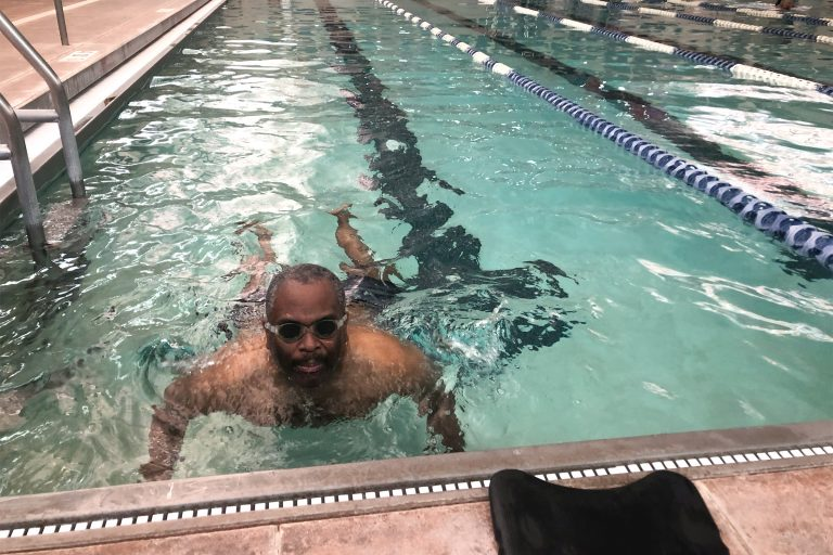 Omar James Brown has autism. He does his laps in the pool but gets excited most when talking about playing basketball. (Cris Barrish/WHYY)