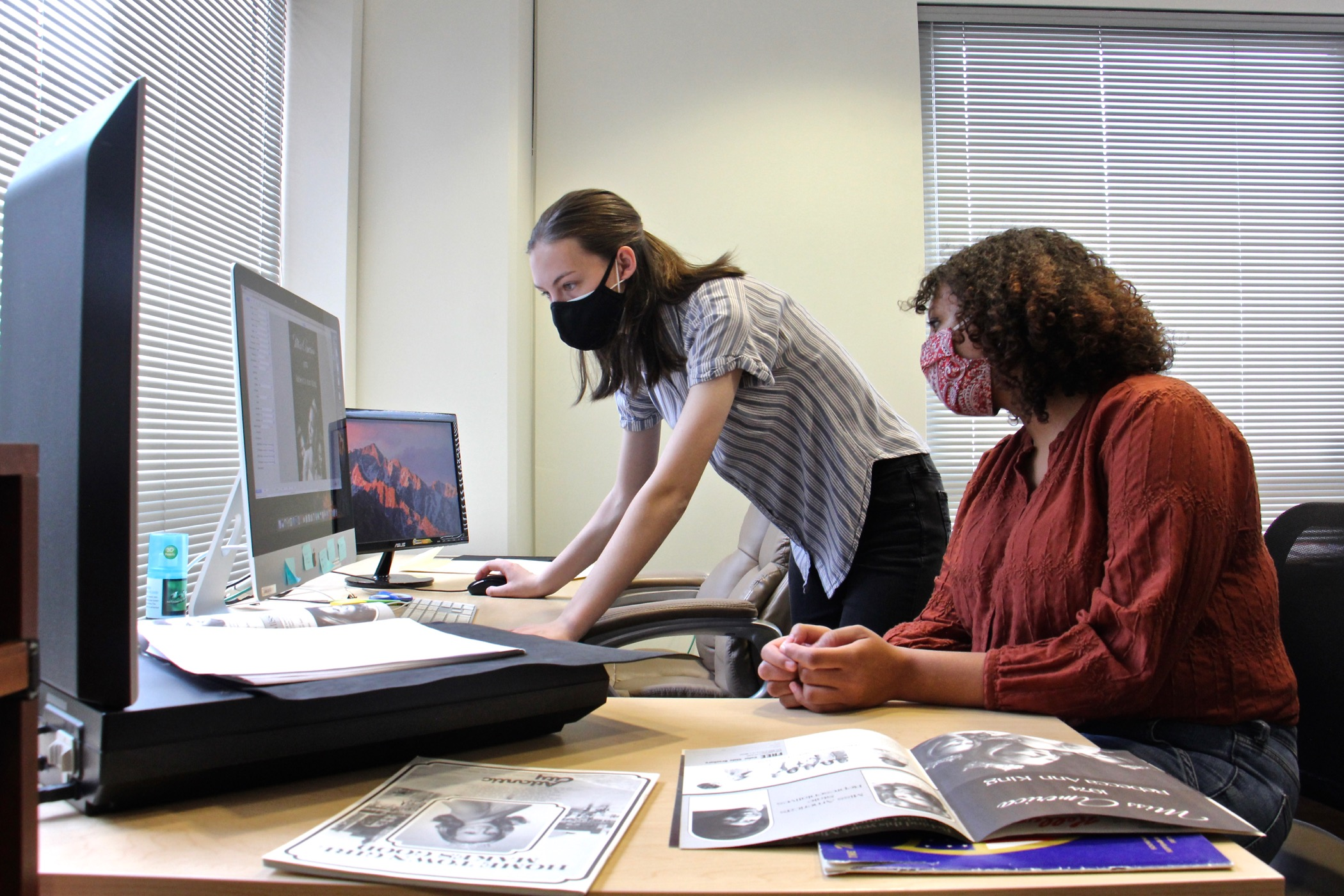 Destiny Hall (right) and Grace Fox work on digitizing program books from the Miss America Organization archives.
