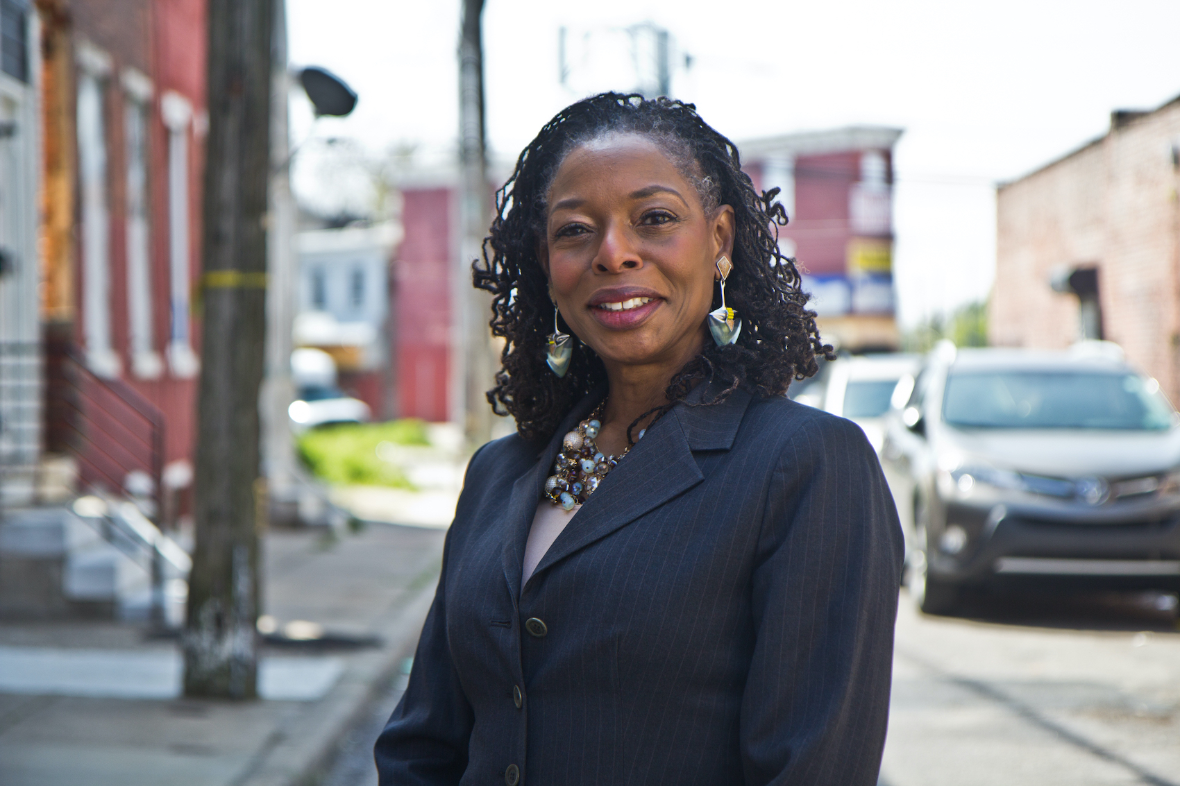 Sandra Dungee Glenn in front of a West Philly property