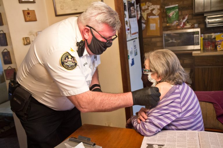 Paramedic Jim McCanns prepares to administer a first dose of the Moderna COVID-19 vaccine to Lucille Breslin at her home in Upper Darby on April 6, 2021. (Kimberly Paynter/WHYY)