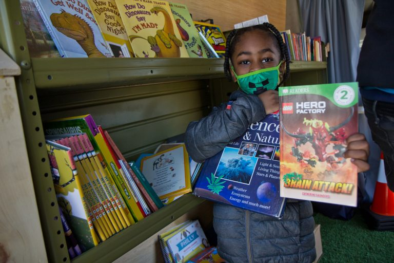 Six-year-old Melvin chose two books from Treehouse Books' mobile library