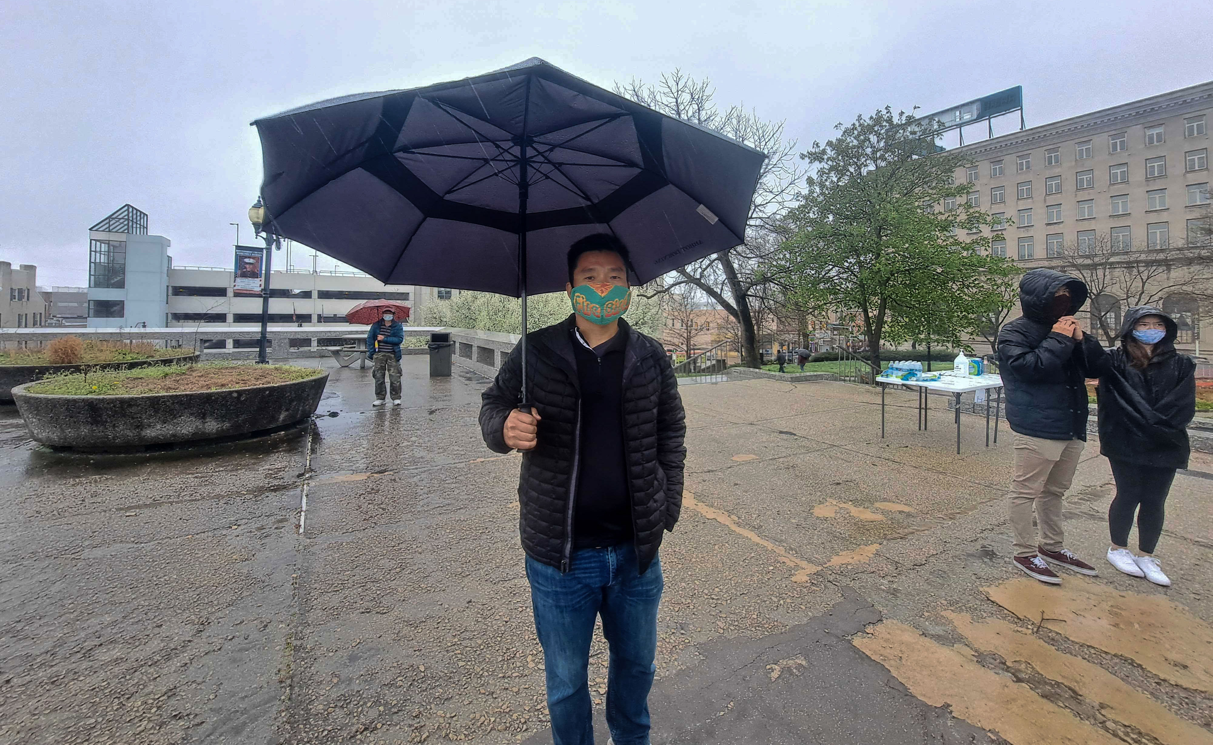 James Kim holds an umbrella while wearing a face mask