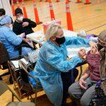 Miriam Palomino, right, receives the COVID-19 vaccine in Paterson