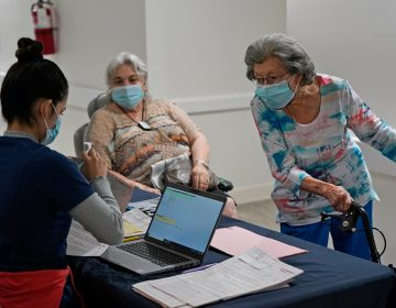 Mitzi Hansrote, right, 86, and Deanna Sutton, center, 83, check in before receiving the COVID-19 vaccine, Thursday, Jan. 21, 2021, at the Isles of Vero Beach assisted and independent senior living community in Vero Beach, Fla. Government officials placed long-term care residents and staff among their top vaccination priorities after they authorized the emergency use of shots from Pfizer and Moderna in late 2020. (AP Photo/Wilfredo Lee)