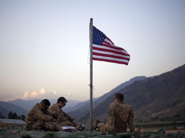 FILE - In this Sept. 11, 2011 file photo, US soldiers sit beneath an American flag just raised to commemorate the tenth anniversary of the 9/11 attacks at Forward Operating Base Bostick in Kunar province. (AP Photo/David Goldman, File)