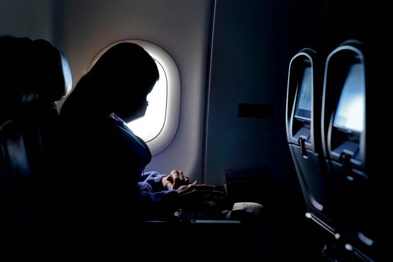A passenger wears a face mask during an airline flight