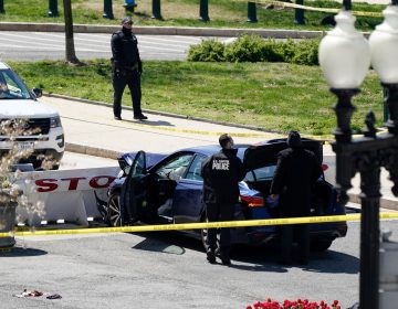 U.S. Capitol Police officers stand near a car that crashed into a barrier on Capitol Hill in Washington, Friday, April 2, 2021. (AP Photo/J. Scott Applewhite)