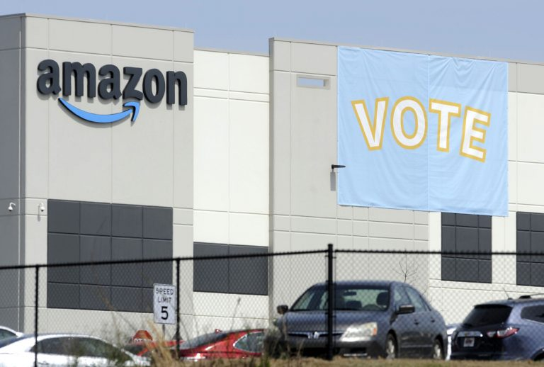 In this Tuesday, March 30, 2021 file photo, a banner encouraging workers to vote in labor balloting is shown at an Amazon warehouse in Bessemer, Ala.
